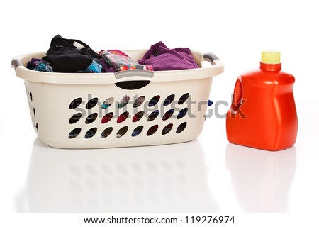 Laundry basket with clean, folded clothes and a bottle of Laundry Detergent isolated on white. - stock photo