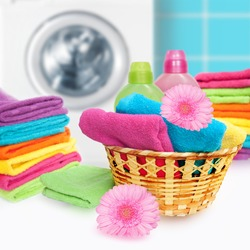 Laundry Basket with colorful towel and washing machine.