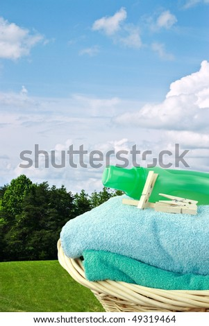 Laundry basket with fresh towels, laundry soap and clothespins against a beautiful summer outdoors background. - stock photo