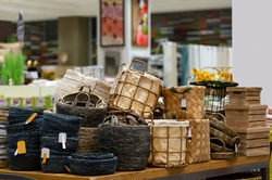 Laundry basket. Woven straw basket, container and boxes on a shelf in store. Bamboo weaving basket and brown Linen on shelf of rack background. Household decoration object made of natural eco material