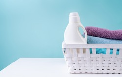 Laundry concept. Laundry basket with a detergent bottle and a pile of clean towels on white table isolated on blue background with copy space