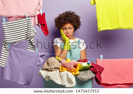 Laundry day concept. Fatigue dissatisfied woman touches cheek and looks away in unhappiness, stands near basket with pile of laundry and detergent, washing lines with hanged wet clothes for drying
