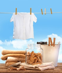 Laundry day with towels, clothespins on table against blue sky