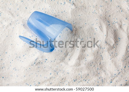 Laundry detergent powder for washing machine and plastic scoop for dosage.