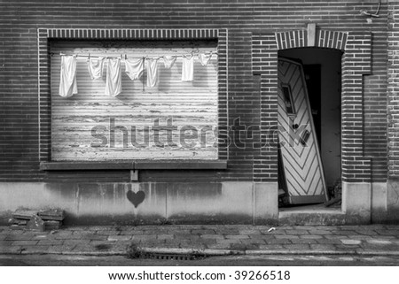 laundry in front of the window of an abandoned house with a broken door