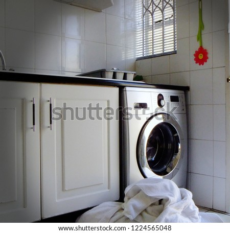 Laundry in front of washing machine in all white kitchen #1224565048
