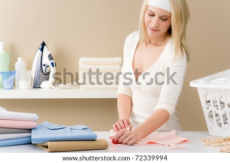 Laundry ironing - woman folding clothes, housework