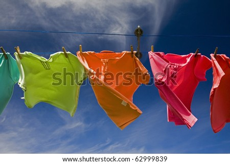 Laundry of pastel colored shirts drying in the wind #62999839