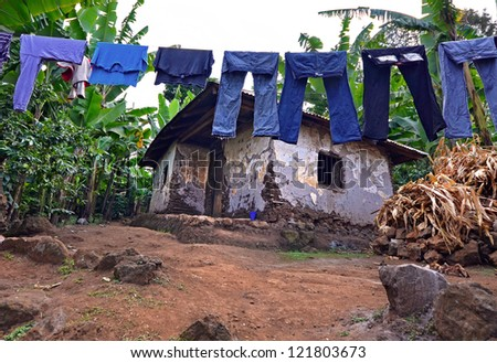 Laundry on a washing lines with mud brick house in a poor area with banana plantation in the background