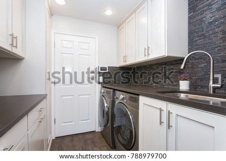 Laundry room boasts white shaker cabinets, brown grey glass tiled backsplash and modern washer and dryer placed under brown counter.  #788979700