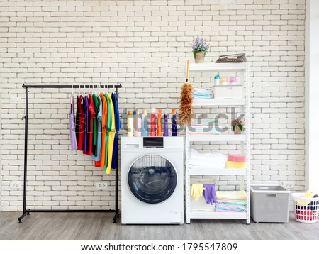 Photo of  Laundry room interior. Utility room with washing machine, cleaning equipment, various home cleaner, clean wipes and colorful clothes hanging on the clothesline on white vintage brick wall background.
