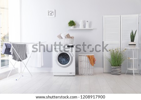 Laundry room interior with washing machine near wall - Shutterstock ID 1208917900