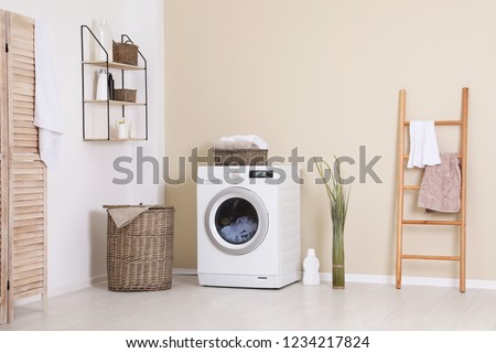 Laundry room interior with washing machine near wall