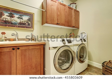 Laundry room with modern appliances, brown vanity cabinet with drawers.