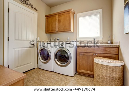 Photo of Laundry room with washer and dryer. Wooden cabinets and tile floor