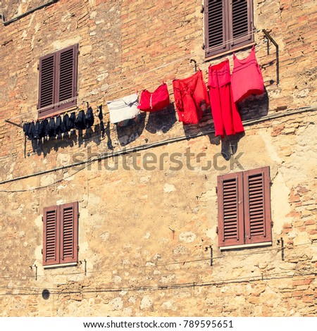 Laundry, sorted by color drying in the sun against an old brick wall and closed shutters. #789595651