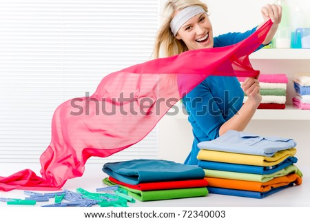 Laundry - woman folding clothes, housework - stock photo