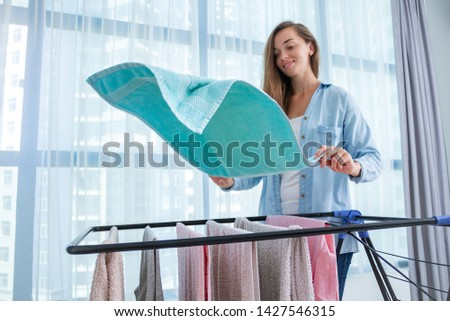 Laundry woman hangs wet clothes on dryer after washing linen at home. Household chores and housekeeping
