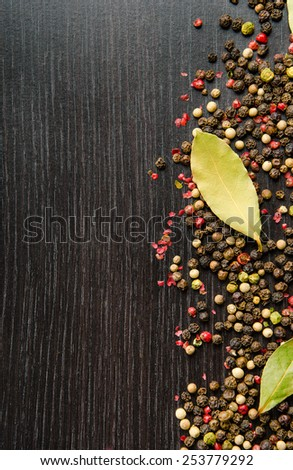 laurel leaves on a mix four pepper on black wooden table