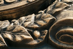 Laurel wreath  close-up dark bronze metal cast background. Vintage leaves and berries sculpture art detail