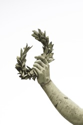 Laurel wreath hand held by a bronze statue on white background