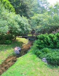 Laurelwood Gardens,Wayne,NJ USA. Wood bridge over small creek.
