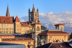 Lausanne city, view over the roofs of the gothic Cathedral and Rumine palace museum (with inscripts Arts, University, Museum, Library) to the snow covered Alps mountains, Switzerland