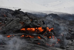 Lava flow at Fagradalsfjall, Iceland. The cooled surface is black while red, molten lava is visible beneath. Steam rises from the lava. White, snowy mountains in the background.