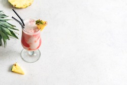 Lava Flow Cocktail - delicious summer tropical drink with rum, strawberry, coconut cream and pineapple juice. Glass of hawaiian cocktail on  light background, copy space.