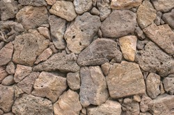 Lava rock exterior wall with pattern/texture in tones of brown,tan,red, and gray/grey.