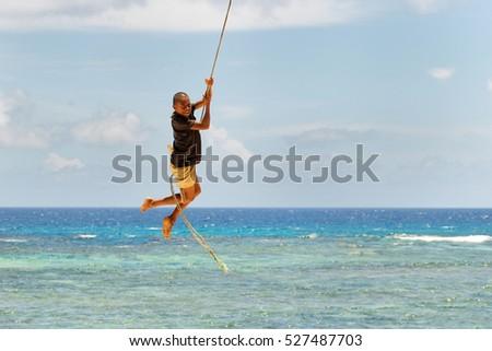 LAVENA, FIJI - NOVEMBER 27: Unidentified boy swings on a rope swing on November 27, 2013 in Lavena village on Teveuni island, Fiji. Taveuni is the third largest island in Fiji. #527487703