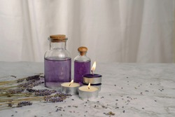 Lavender aroma scent in clear glass bolttles with candle light on with lavender flower on mable table and curtain background in warm tone, Aroma therapy with purple lavender concept.