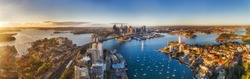 Lavender bay from lower North Shore on Sydney harbour agains major city CBD landmarks around the Sydney Harbour bridge in soft warm morning light seen from mid-air over roof tops.