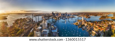 Lavender bay from lower North Shore on Sydney harbour agains major city CBD landmarks around the Sydney Harbour bridge in soft warm morning light seen from mid-air over roof tops. #1360015517