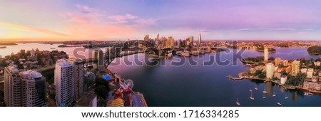 Lavender bay on Sydney Harbour in front of city CBD and major landmarks in wide aerial panorama at sunrise.