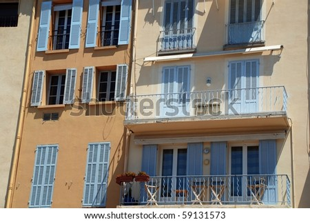 Lavender blue colored shutters on yellow stucco