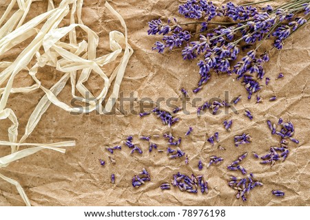 Lavender floral background with fresh flowers and aromatherapy seeds with natural raffia over grunge brown recycled craft paper wrap