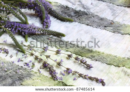 Lavender flowers and twigs on ornate green fabric
