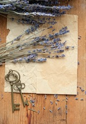 lavender flowers, bronze vintage keys and old paper on rustic wooden table. romantic nostalgic composition. flat lay. copy space. flat lay