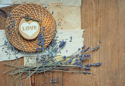 lavender flowers, heart decor, key and old paper on rustic wooden background. romantic nostalgic composition. copy space