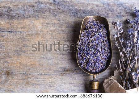 Lavender flowers in an antique scoop and lavender bouquet on wooden background. Top view.  #686676130