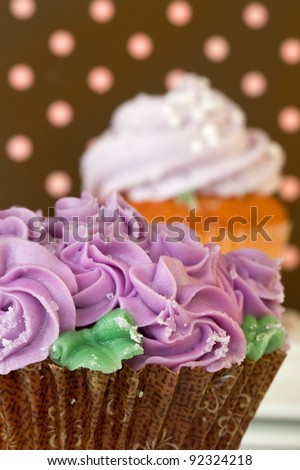 Lavender Frosted Cupcake Against A Polka Dot Background