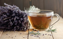 Lavender herbal leaf tea in a glass cup with lavender bouquet and herb leaves nearby on rustic wooden table, closeup, copy space, herbal drinks and naturopathy concept