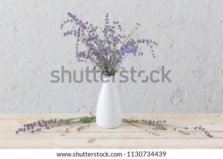 lavender in white vase on wooden table