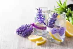 Lavender lemonade drink in jar on white wooden table