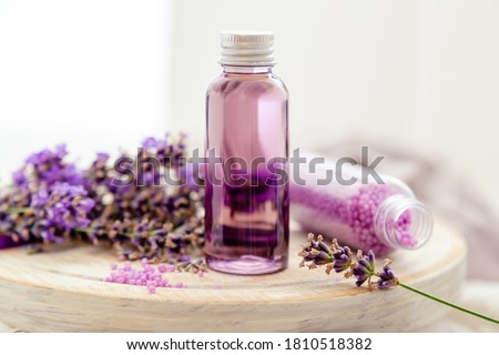 Lavender liquid. Bath cosmetics products in bottles on white wooden rustic board, fresh lavender flowers, soap, bath beads. Lavender essential oil, natural spa products. Aromatherapy treatment Foto stock ©