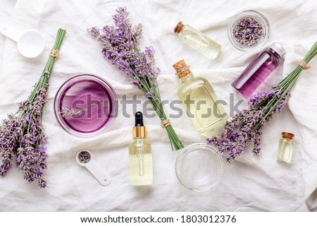 Lavender oils serum and lavender flowers on white fabric. Skincare cosmetics products. Set natural spa beauty products. Lavender essential oil, serum, body butter, massage oil, liquid. Flat lay