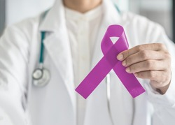 Lavender purple awareness ribbon (symbolic bow color for all kinds of cancer) on doctor's hand support for World cancer day, and National cancer survivor month, lupus illness charity campaign