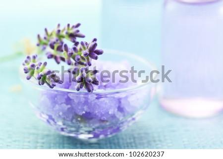 Lavender salt with aromatherapy oil on light blue background