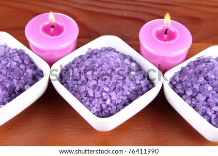 Lavender spa salt and lavender candles on a wooden background